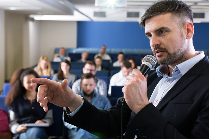 Close-up of a young academic teacher holding a microphone and pointing at something during college classes