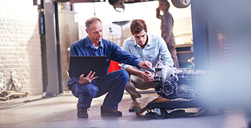 Mechanic and customer with laptop examining engine in auto repair shop