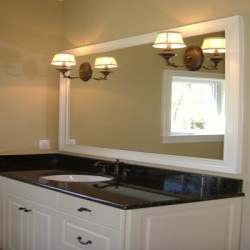 Glossy black counter tops bring drama to this Chicago bathroom remodel by Home Services Direct.