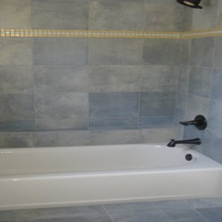 Clean tile detailing brings character to this bathroom remodeling project by Home Services Direct.