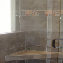Built in ledges create convenient storage for this Chicago bathroom remodel by Home Services Direct.