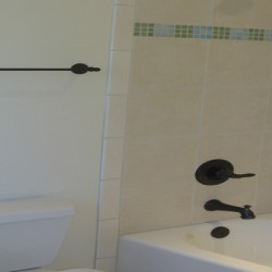 Light tiling and dark hardware contrast beautifully in this Chicago bathroom remodel by Home Services Direct.