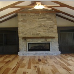 The floor to ceiling stone around this fireplace creates a focal point for this Chicago home remodeling project by Home Services Direct.