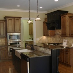A variety of paint colors and cabinet designs add drama to this Chicago kitchen remodel by Home Services Direct.