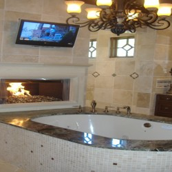 A mounted television and gorgeous fireplace bring luxury to this Chicago bathroom remodel by Home Services Direct.