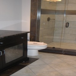 Contrasting colors and glass details bring a modern aesthetic to this Home Services Direct bathroom remodel in Chicago.