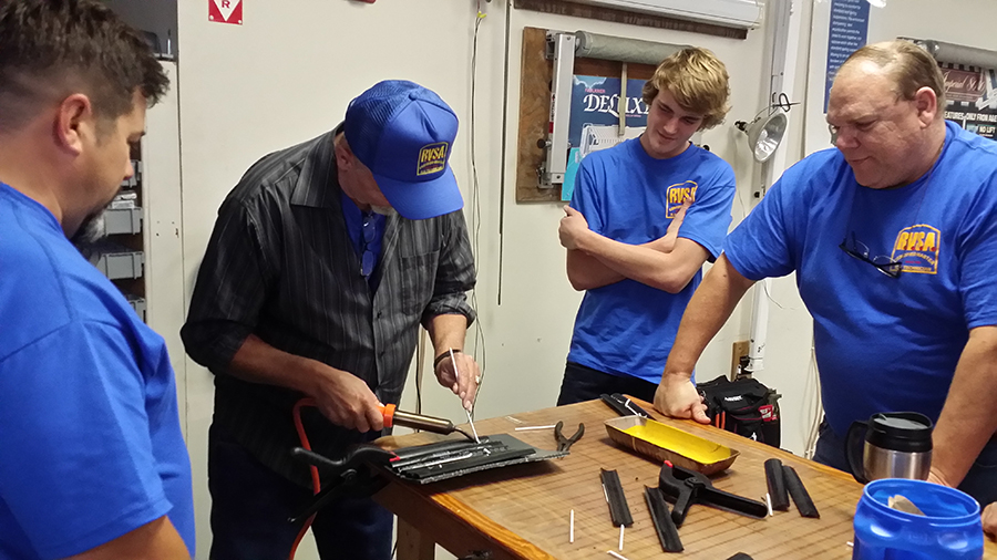 Students taking turns learning how to plastic weld